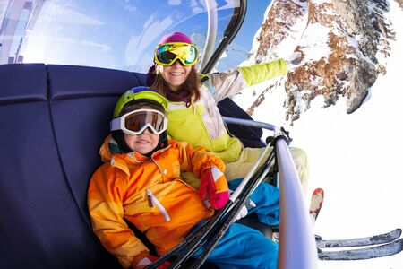 ski lift: Happy young woman and little 4 years old boy sitting on the chair on ski lift smiling and wearing ski masks with mountain on background