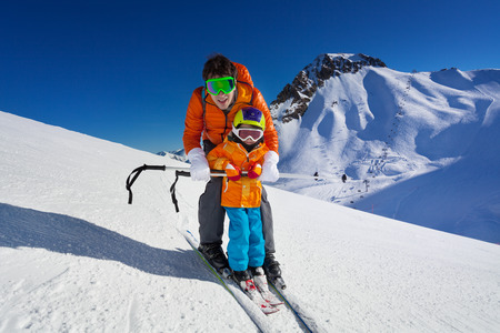 Little boy learns to ski on mountain resort with instructor helping to learn how to turn with mountain on background