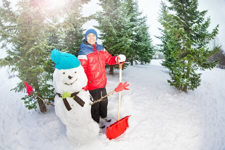 Arabian boy with shovel standing near snowman photo