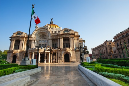 Palace of fine arts facade and Mexican flag Editorial