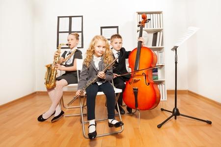 niños sentados: Felices los niños tocando instrumentos musicales en conjunto Foto de archivo