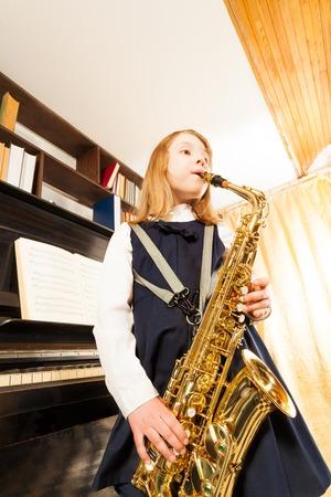 Girl in school uniform playing on alto saxophone photo