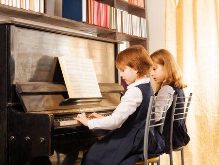 Two cheerful beautiful small girls playing piano photo