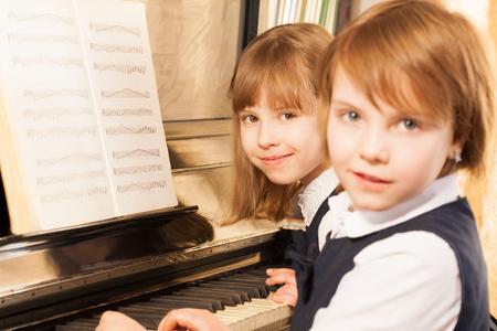 tocando piano: Sonriendo hermosas ni�as peque�as que juegan el piano Foto de archivo