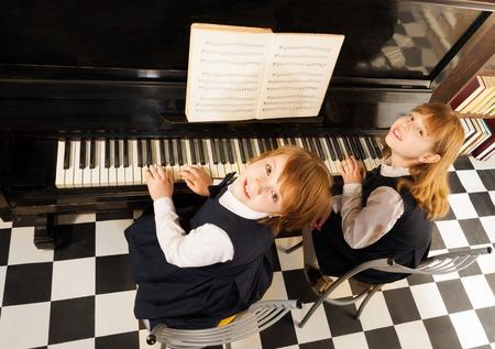 piano: Vista desde la parte superior de las niñas con uniformes tocando el piano