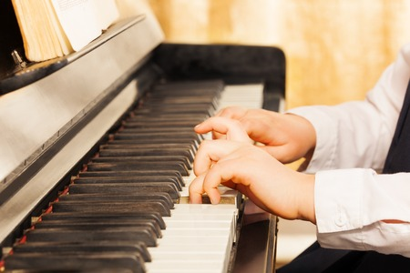 child hand: Childs hands playing on the piano-keys