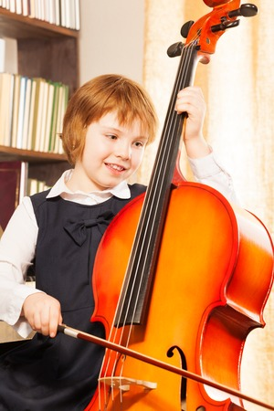 Happy girl in school uniform playing on the cello photo