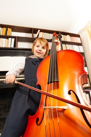 the view from below: View from below of girl in dress playing on cello Stock Photo