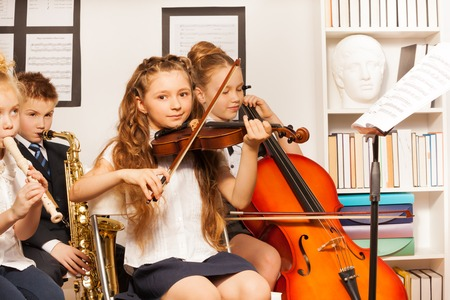 violin: Group of kids playing musical instruments indoors