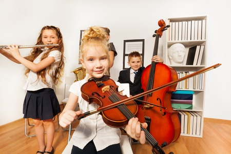 kid portrait: Performance of kids who play musical instruments Stock Photo