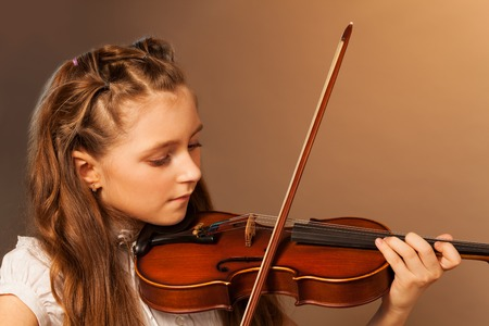 Half-face view of beautiful girl playing violin Stock Photo