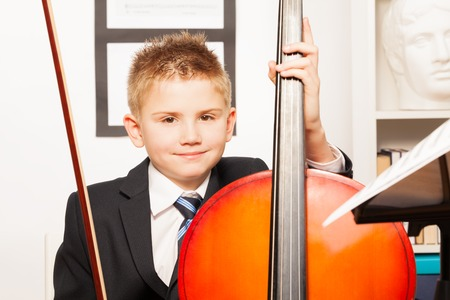 fiddlestick: Muchacho que sostiene fiddlestick Sonre�r, jugar violoncello