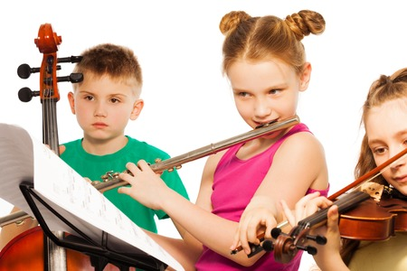 Group of cute kids playing on musical instruments photo