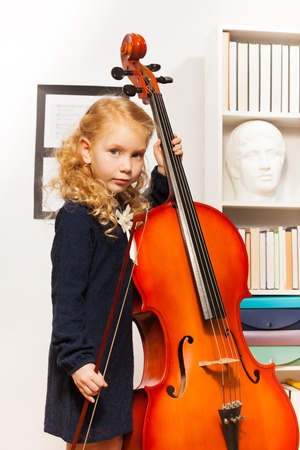 kids dress: Girl with curly hair holds string to play cello