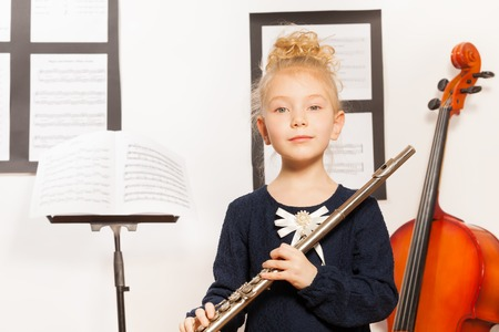 Small blond girl with flute stands near the cello photo
