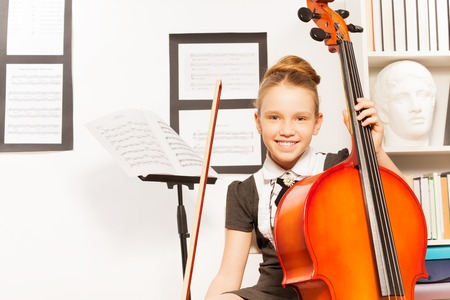 violoncello: Smiling girl holds string to play violoncello