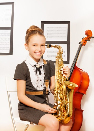 Happy girl in school dress with alto saxophone photo