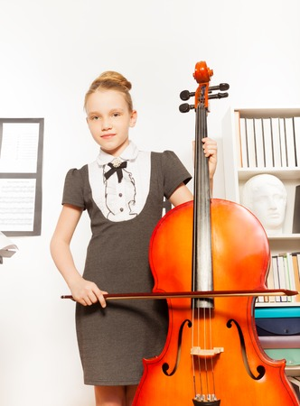 violoncello: Beautiful girl holding and playing violoncello