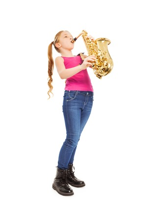 Small girl holding and playing alto saxophone