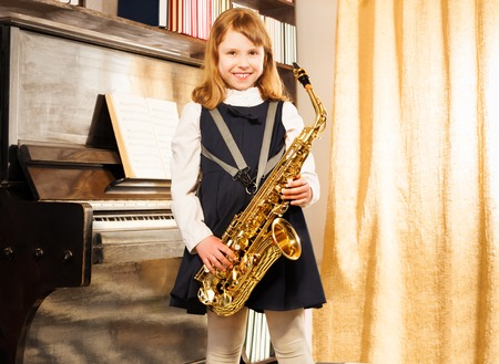 school play: Happy girl in school uniform holds alto saxophone