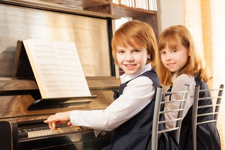 Cheerful beautiful small girls play piano together photo