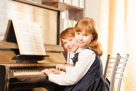 Two cute small girls in uniforms playing piano photo
