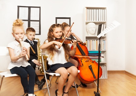niños jugando en la escuela: Niños alegres que tocan los instrumentos musicales
