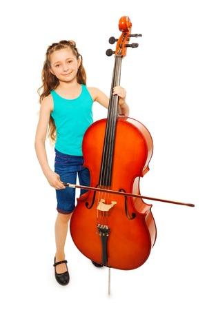 긴 머리를 가진 소녀는 첼로를 연주하기위한 문자열을 보유하고 있습니다. 스톡 콘텐츠