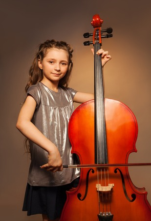 Classy girl with long hair holding cello to play Stock Photo