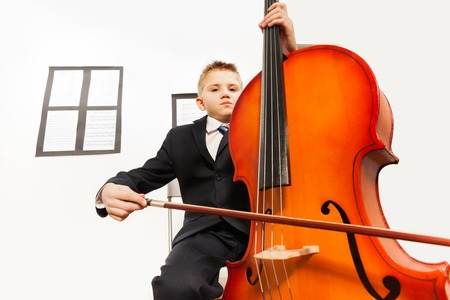 Boy playing violoncello sitting on the chair photo