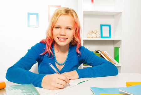 kids writing: Happy girl smile, write in textbook doing homework