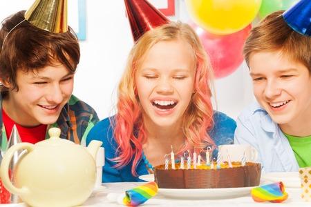 pasteles de cumplea�os: Muchacha adolescente velas j�venes soplado con amigos r�en