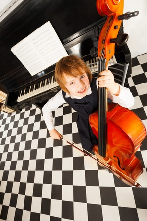 Cheerful small girl in dress playing on the cello photo