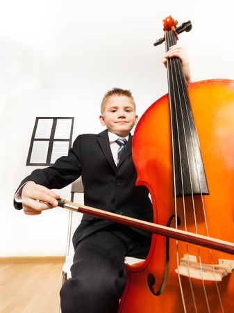 Portrait of boy playing cello sitting on the chair