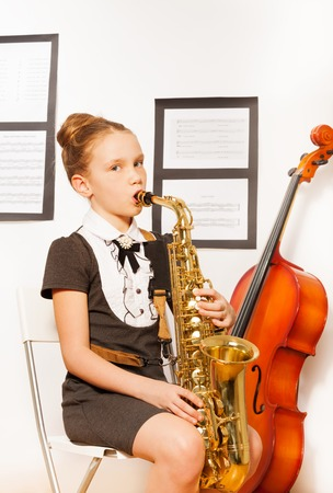 alto: Beautiful girl in dress holding alto saxophone
