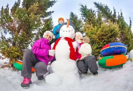 the view from below: View from below of kids sitting close to snowman Stock Photo