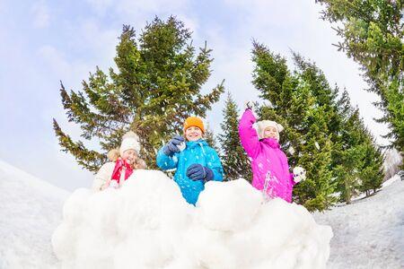 palle di neve: Ragazze e ragazzo a giocare palle di neve gioco in foresta Archivio Fotografico