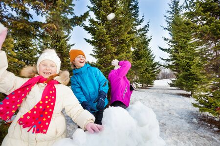 girl fight: Group of happy kids throw snowballs during fight Stock Photo