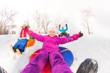 sledging people: Girl and kids sliding down the hill on tubes