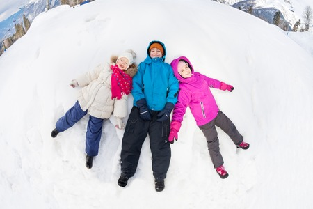 legs apart: Three kids lay on the snow with legs apart Stock Photo
