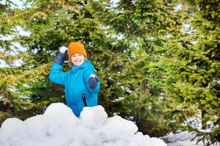 snowballs: Happy boy in blue winter jacket playing snowballs