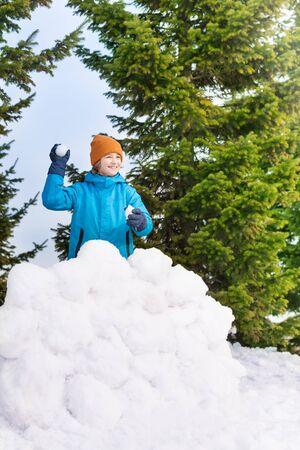 palle di neve: Ragazzo in giacca blu inverno lanciando palle di neve