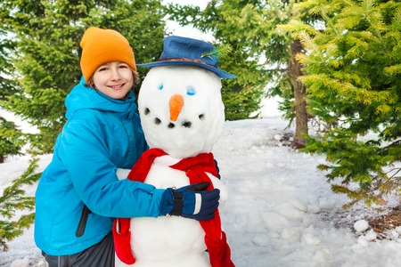 red scarf: Boy build snowman with red scarf during winter day