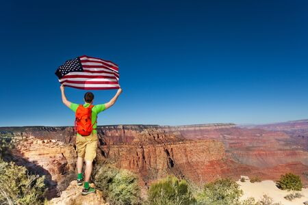 Grand Canyon National Park and man with US flag Stock Photo