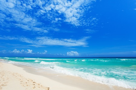 footsteps on white sand and beautiful waves Cancun