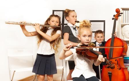 Schulkinder spielen Musikinstrumente zusammen
