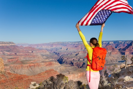 american flags: Woman with rucksack holding American flag, USA
