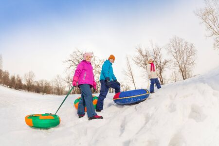 sledging people: Children walking up snowy hill with colorful tubes