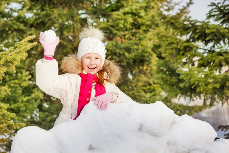 girl fight: Laughing girl with snowball behind snow wall