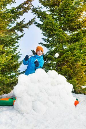 snowballs: Ragazzo di risata in giacca invernale blu gioca le palle di neve